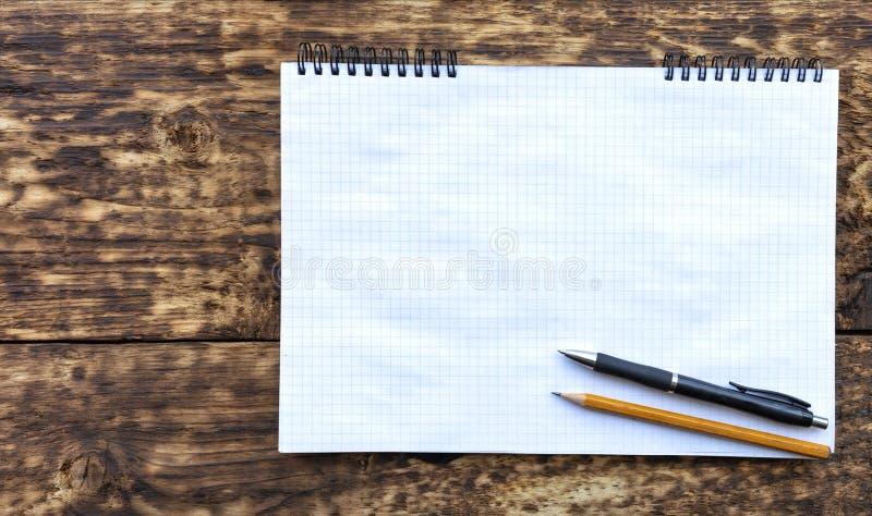 Caderno vazio com um lápis e pena preta em uma superfície de madeira estrutural velha imagens de stock royalty free