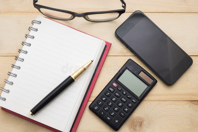 Caderno vazio da vista superior, calculadora, pena, vidros e telefone esperto fotografia de stock royalty free