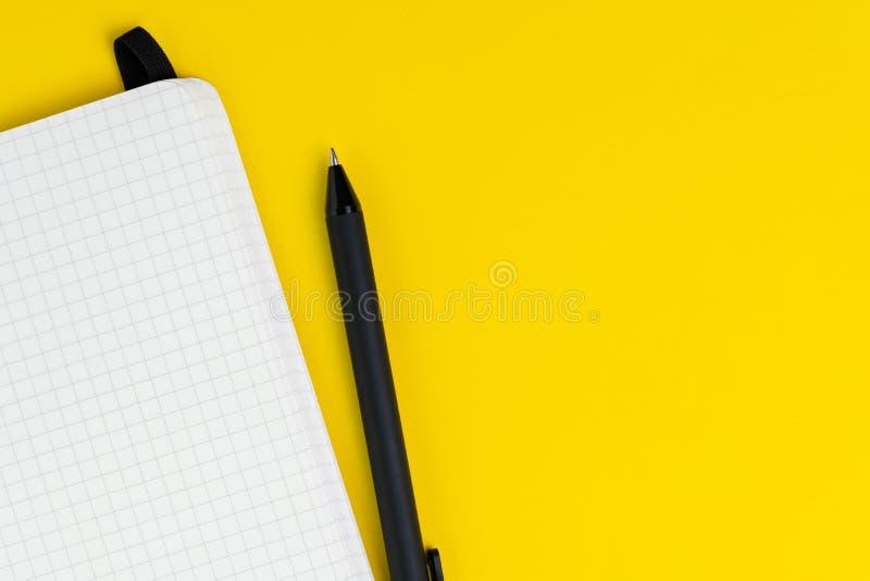 Caderno vazio de abertura da página do papel de gráfico com a pena no backgrond amarelo contínuo usando-se como o desempenho empr fotos de stock
