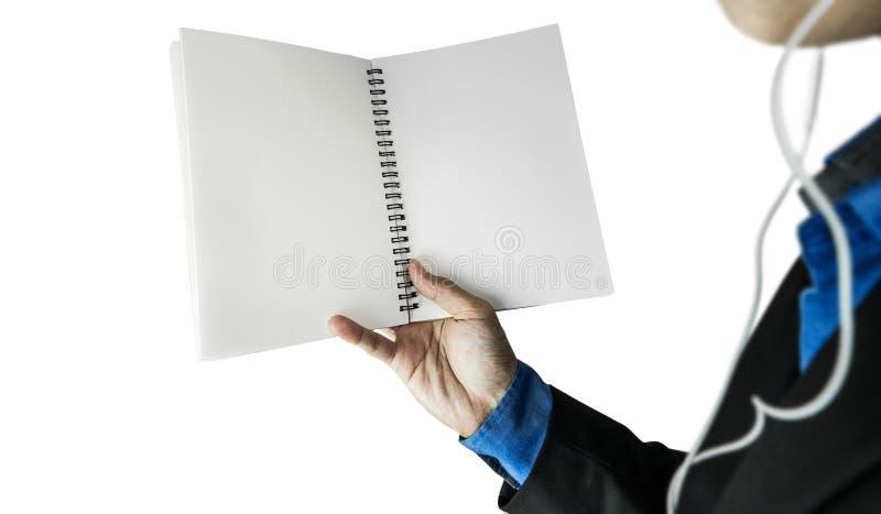 Caderno vazio de abertura em uma mão vestindo dos fones de ouvido do indivíduo, foco seletivo, isolado no fundo branco fotos de stock royalty free