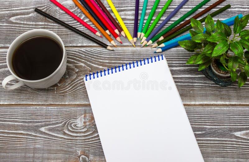 Caderno vazio e copo colorido do lápis e de café no fundo de madeira da tabela do escritório fotos de stock