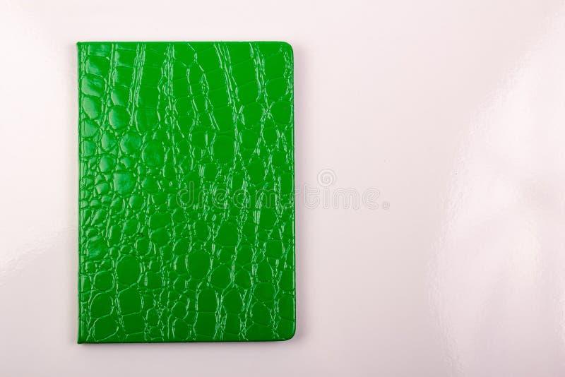 Caderno verde com a pena no fundo branco imagens de stock royalty free