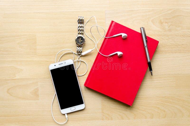 Caderno vermelho da placa da capa do livro com pena na tabela de madeira e em um chá moderno do telefone dos auriculares do relóg imagem de stock
