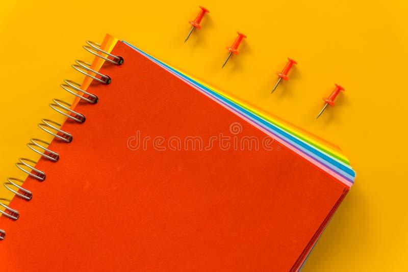 Caderno vermelho no fundo cor-de-rosa pastel amarelo fotografia de stock