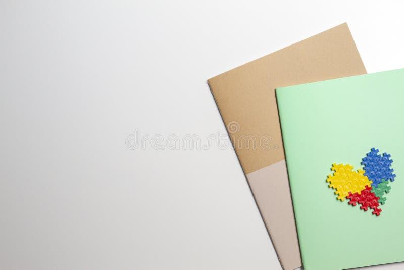 Cadernos coloridos e coração feitos de tijolos plásticos da construção no fundo branco imagem de stock royalty free