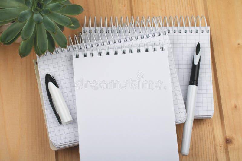 Cadernos com a pena à moda na superfície de madeira foto de stock