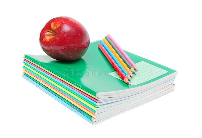 Cadernos, lápis e maçã imagens de stock royalty free