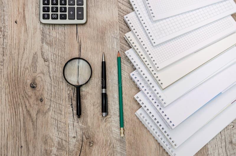 Cadernos, pena, lápis, lente de aumento e uma calculadora em um fundo de madeira foto de stock royalty free