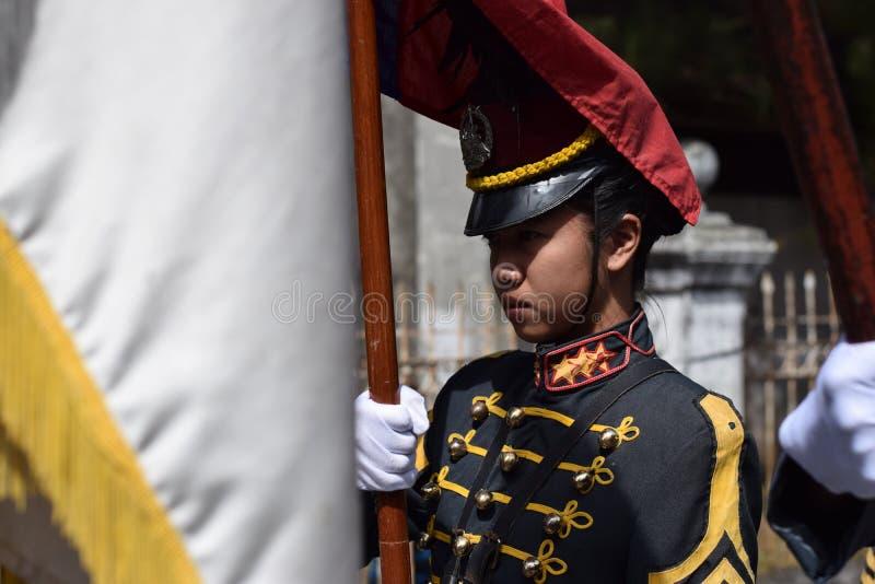 Cadet militaire d'université femelle sur la formation debout tenant le drapeau national photos libres de droits