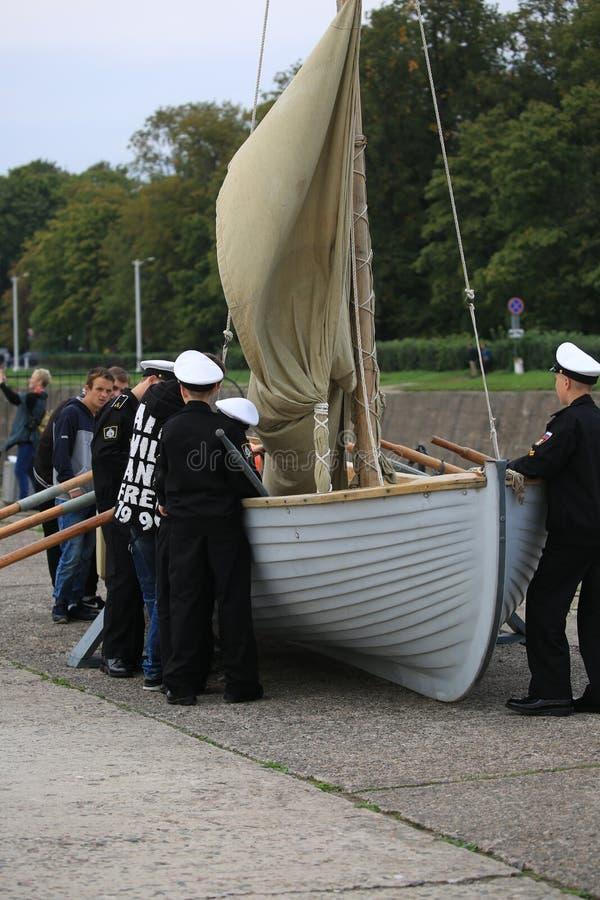 Cadete do corpo naval do cadete de Kronstadt e dos visitantes civis perto do barco da enfileiramento-navigação foto de stock royalty free