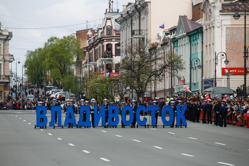 Cadets de l'université maritime porter le Vladivostok de inscription sur la rue principale de Vladivostok en l'honneur de Victory image libre de droits