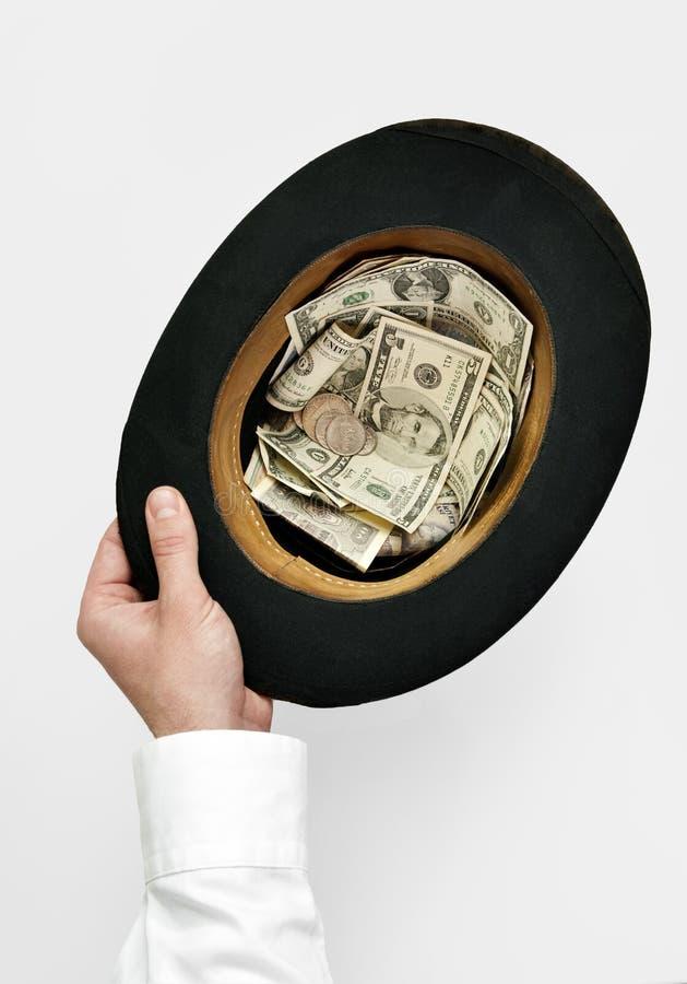 Cadger概念。拿着有金钱的手老顶帽子 库存图片