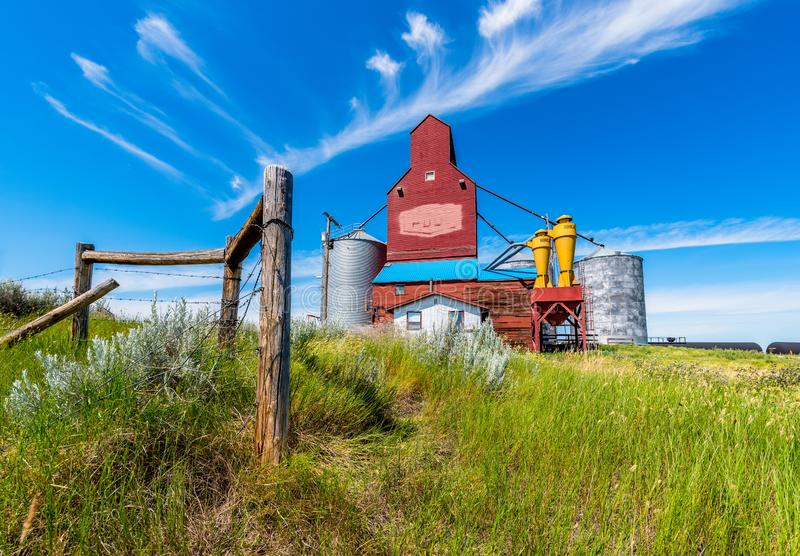 Cadillac, SK/Canada: The historic Cadillac grain elevator in Saskatchewan, Canada. With fence posts and grass in the foreground stock image