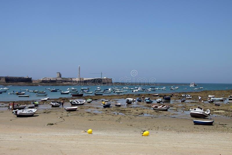 Boats off the Atlantic coast near the fortress of San Sebastian in Cadiz. stock photo