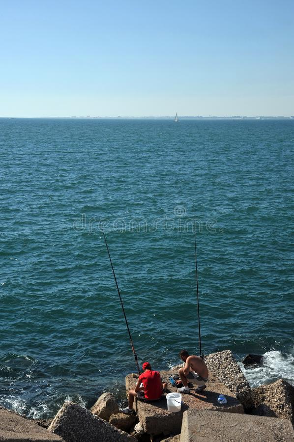 Fishermen are fishing in the harbor of the seaport of Cadiz. stock image
