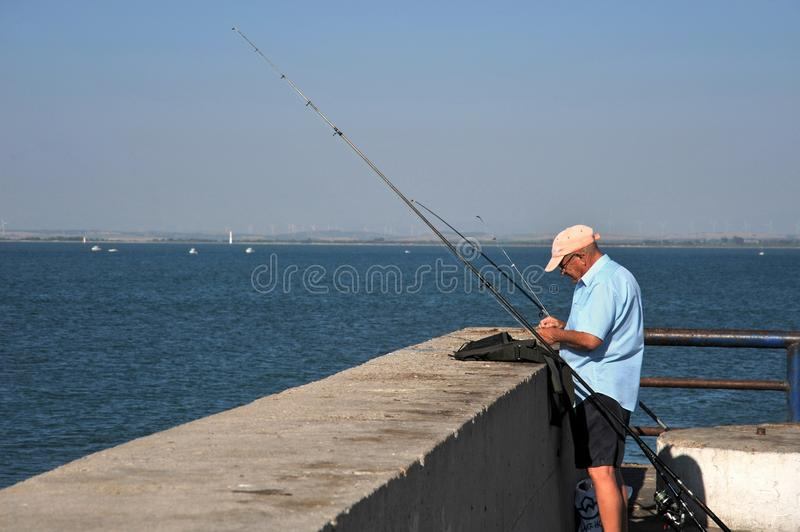 Fishermen are fishing in the harbor of the seaport of Cadiz. royalty free stock photo