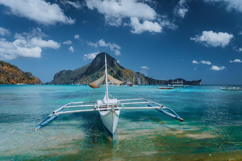Cadlao panorama with Traditional filippino banca boat in front. Exotic tropical El Nido bay, Palawan Island, Philippines.  royalty free stock image
