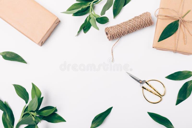 Cadre étendu plat de fête du feuillage luxuriant, des ciseaux, du jute et des boîtes enveloppés en papier brun d'eco, l'espace de photographie stock