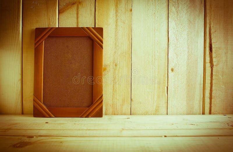 Cadre antique de photo sur la table en bois au-dessus du fond en bois image stock