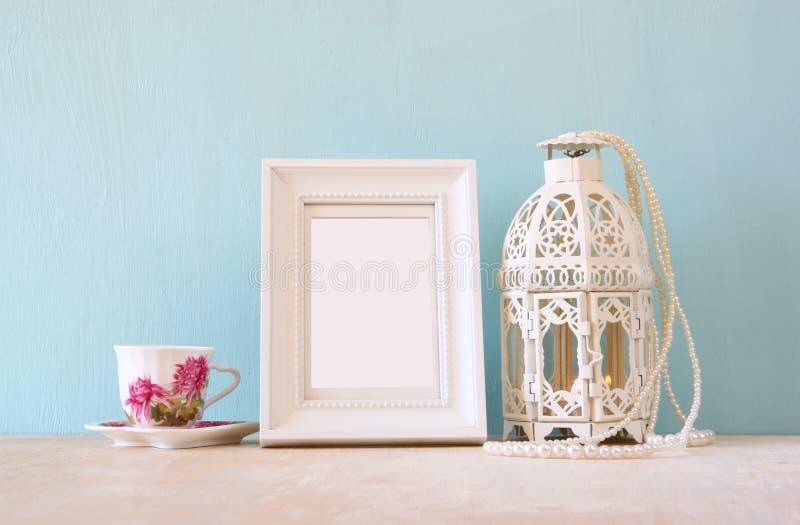 Cadre blanc classique de vintage sur la table en bois avec la tasse et la lanterne de porcelaine photos libres de droits