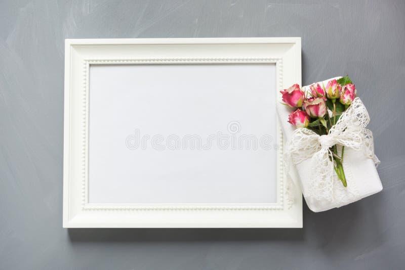 Cadre blanc de photo avec le cadeau et les roses femelles sur le fond neutre gris Vue supérieure Copiez l'espace image stock