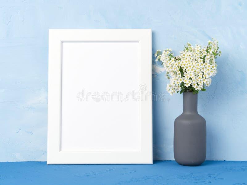 Cadre blanc vide, fleur dans le vaze sur la table bleu-foncé contre le mur en béton bleu avec l'espace de copie Voir les mes autr photo libre de droits