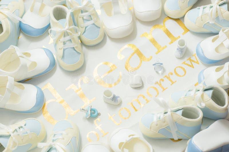 Cadre bleu de petits chaussons de bébé garçon sur un fond blanc de tissu Accueil de la partie de douche nouveau-née Rêve de demai image libre de droits