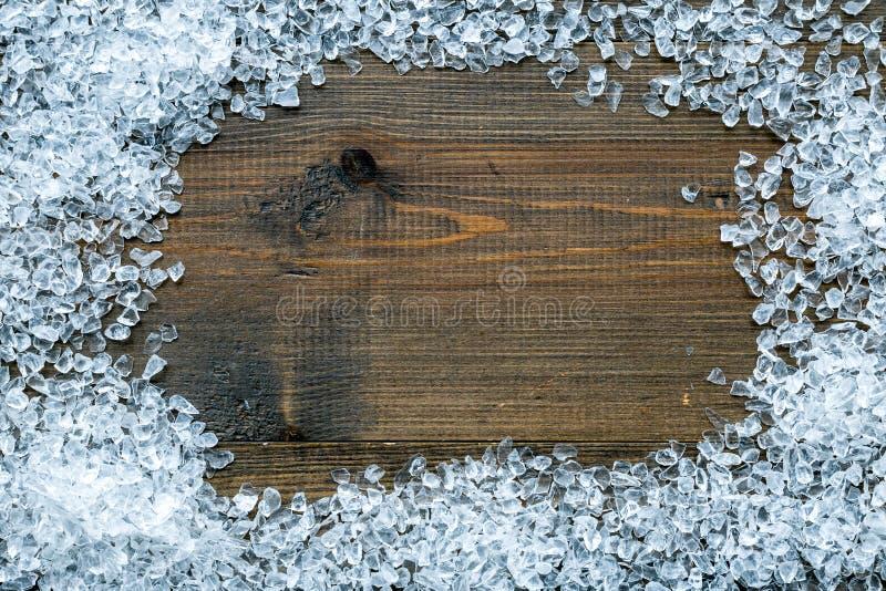 Cadre brisé de glaçons sur la moquerie en bois de vue supérieure de table de barre  photographie stock