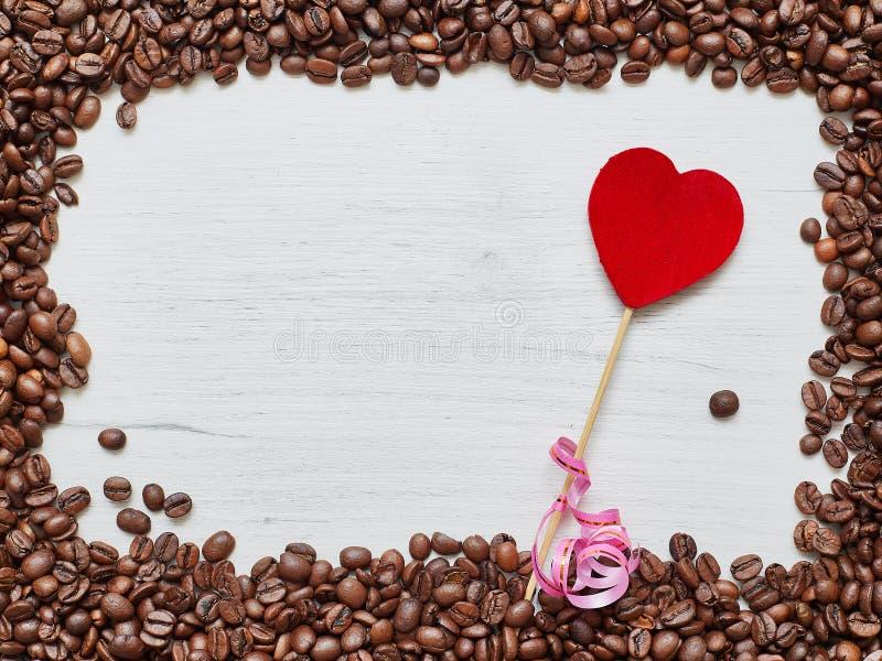 Cadre carré des grains de café avec le coeur rouge sur une table en bois, jour du ` s de Valentine photographie stock libre de droits