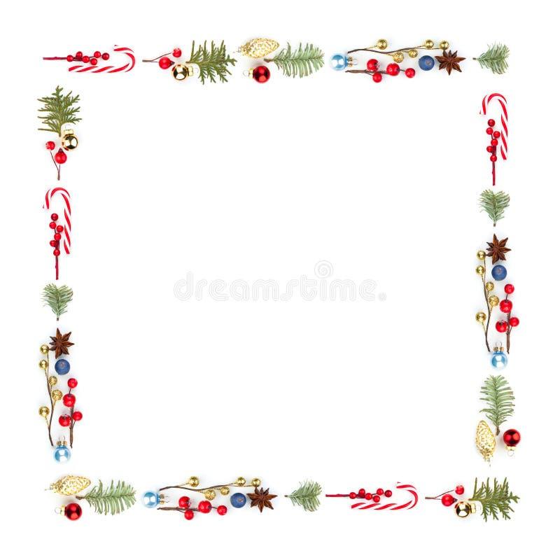 Cadre coloré de composition en place de Noël avec la lucette de Noël, les baies rouges de houx, le décor d'or et la branche verte images stock