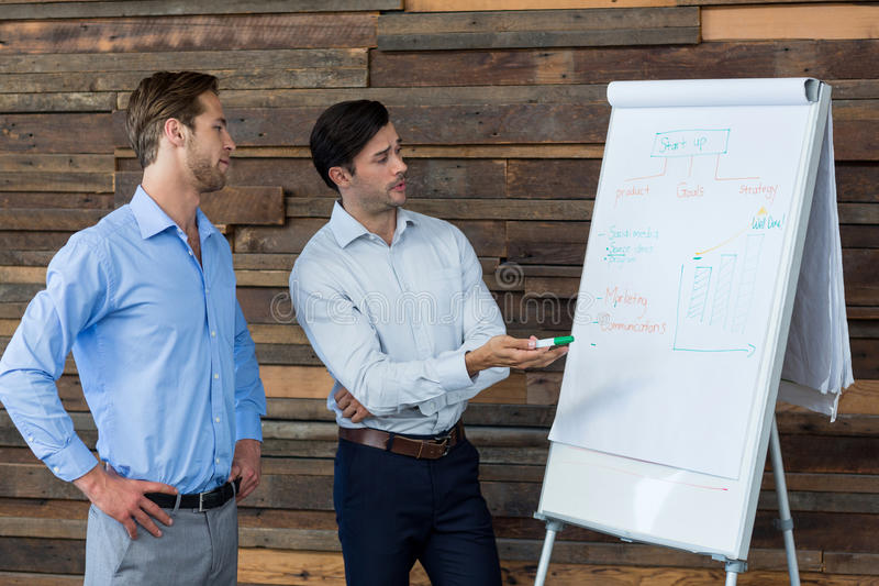 Cadre commercial de deux mâles discutant au-dessus d'un tableau de conférence photos libres de droits