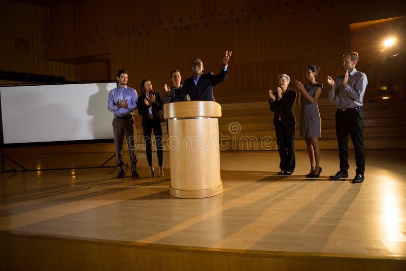 Cadre commercial donnant un discours tandis que collègues applaudissements images libres de droits