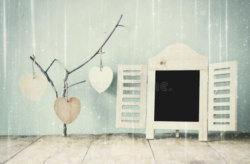Cadre décoratif de tableau et coeurs accrochants en bois au-dessus de table en bois préparez pour le texte ou la maquette rétro i photos libres de droits