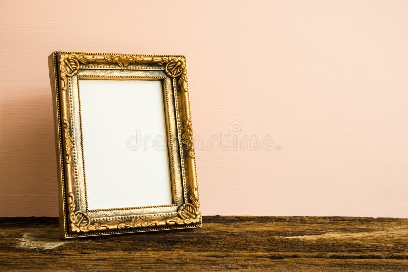 Cadre d'or de photo de vintage sur la vieille table en bois au-dessus du Ba rose de mur photographie stock libre de droits