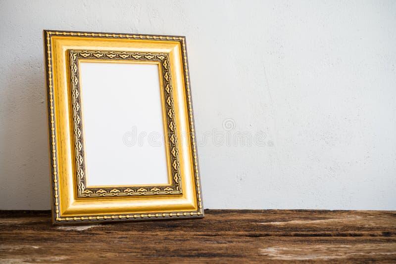 Cadre d'or de photo de vintage sur la vieille table en bois au-dessus du mur blanc b images libres de droits
