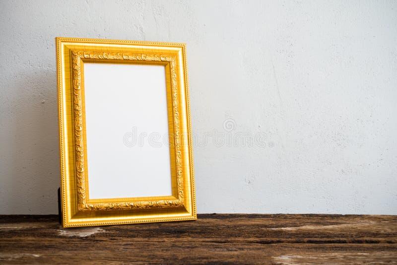 Cadre d'or de photo de vintage sur la vieille table en bois au-dessus du mur blanc b photo stock