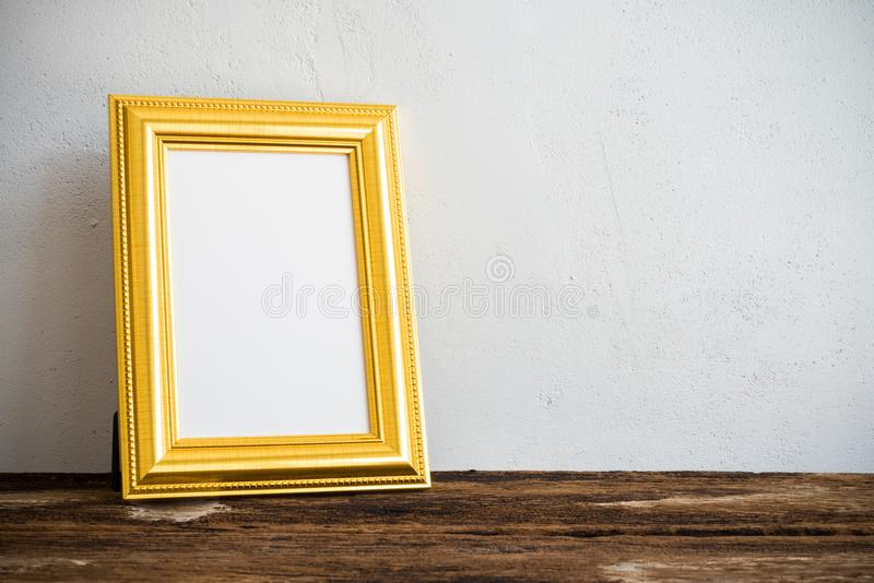 Cadre d'or de photo de vintage sur la vieille table en bois au-dessus du mur blanc b photographie stock
