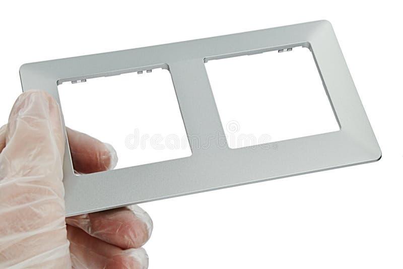 Cadre d'interrupteur de lampe jumeau fait de matière plastique de conception ressemblant à l'aluminium, tenu à disposition avec l image libre de droits