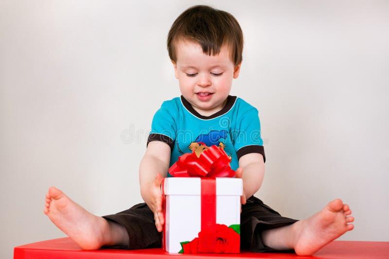 Cadre de cadeau heureux d'ouverture de garçon d'enfant en bas âge photo libre de droits