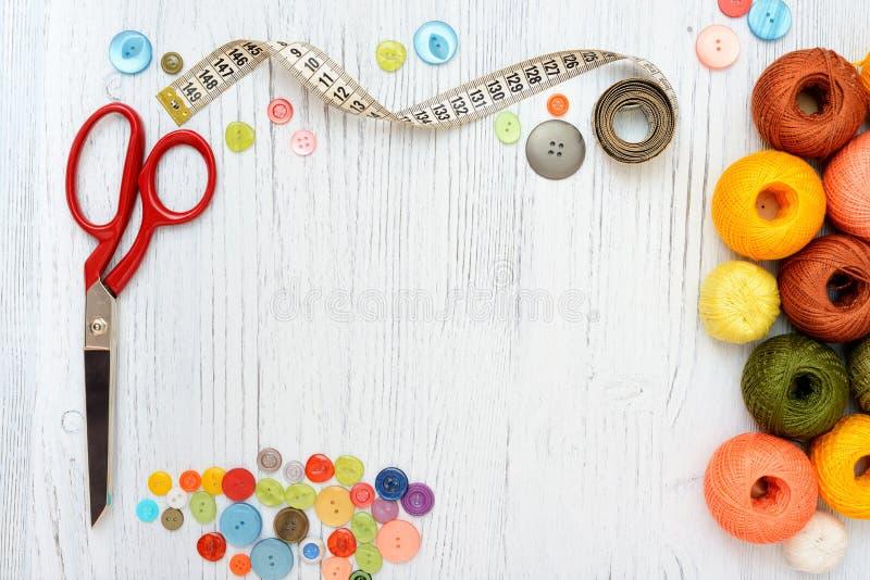 Cadre de Copyspace avec les outils et les accessoires de couture sur le fond en bois blanc images stock