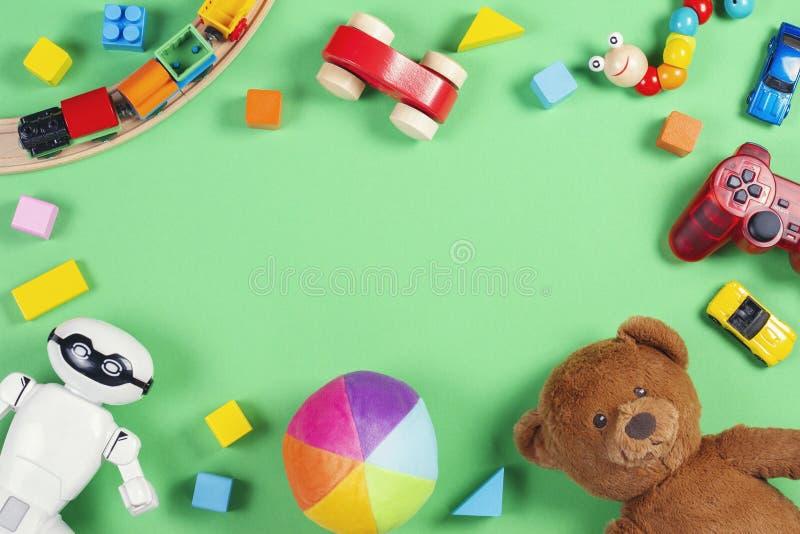 Cadre de jouets d'enfants de bébé avec l'ours de nounours, voitures de jouet, robot, briques colorées, cubes sur le fond rose images libres de droits