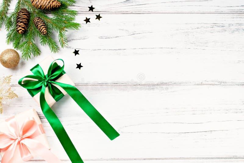Cadre de Noël aux branches de sapin, cadeaux enveloppés dans des couleurs roses et vertes, confettis Plaque de Noël, espace de co photographie stock