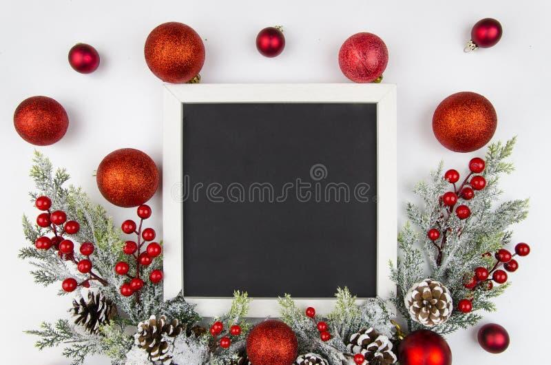 Cadre de Noël avec des branches de baie de Noël décorées des boules rouges Maquette catégoriquement trandy Vue supérieure photographie stock libre de droits