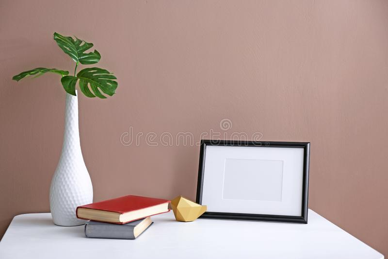 Cadre de photo avec des livres et des feuilles vertes dans le vase sur la table blanche sur le fond de couleur image stock