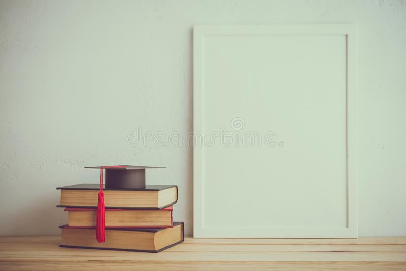 Cadre de photo et livres, chapeau de graducation sur le fond blanc de mur, photo stock