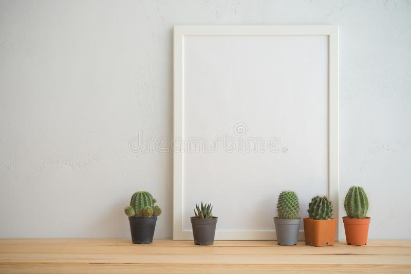 Cadre de photo et maquette de pots de cactus avec le fond blanc de mur, c image stock