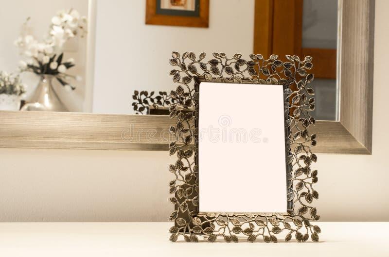 Cadre de tableau fleuri sur la réflexion blanche de table dans le miroir Bla image stock
