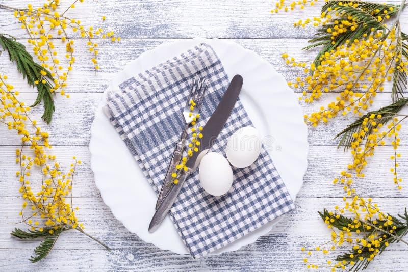 Cadre des tables de Pâques Oeufs blancs, serviette en lin, assiette blanche, fleurs de mimosa et couverts sur une table en bois photos libres de droits