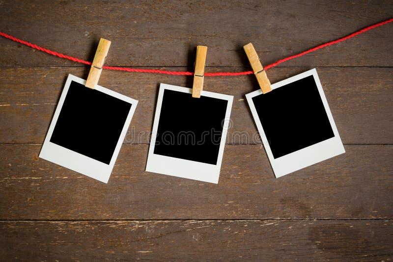 Cadre en blanc de la photo trois accrochant sur le fond en bois photos libres de droits