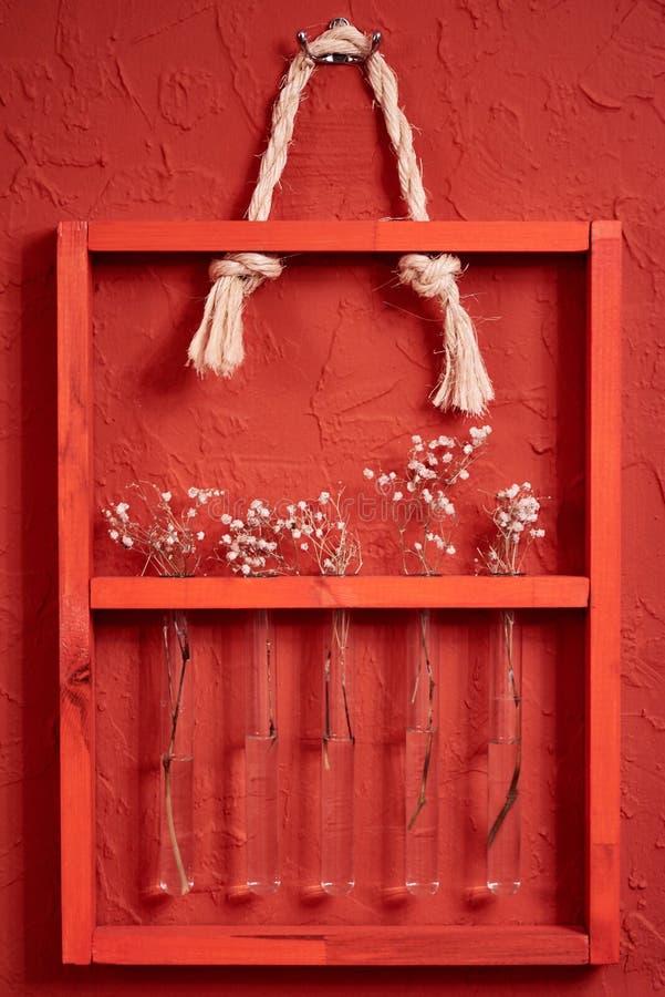 Cadre en bois avec des fleurs sur le mur rouge photo libre de droits